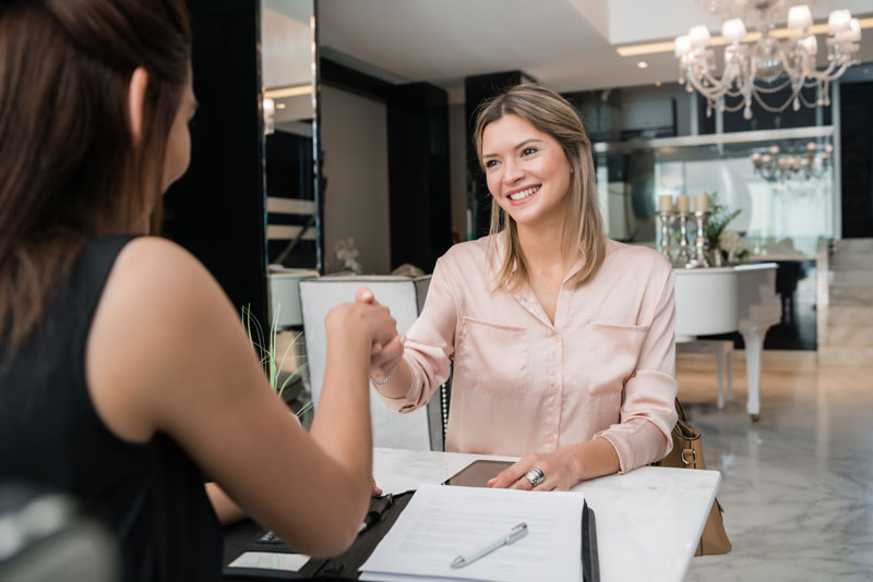 Two businesswomen having meeting at hotel lobby.